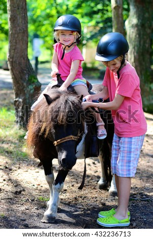Young children enjoying horse back riding activity. Group of school age kids taking care about their pony and learning how to feed the animal. Summer camp for active holidays.  - stock photo
