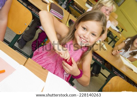 Young children in a yellow classroom. Girl is pointing her pencil. - stock photo