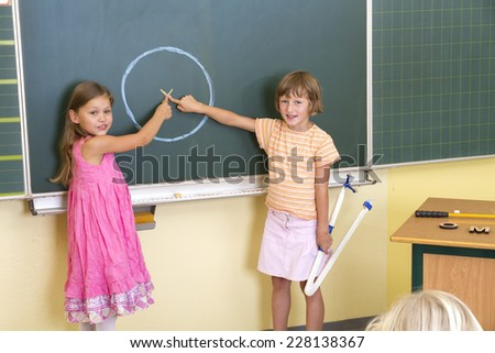 Young children in front of a blackboard. - stock photo