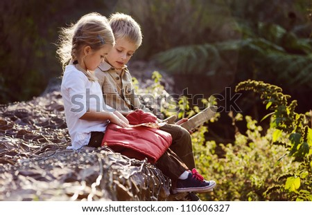 young children playing outdoors, happy brother and sister having fun - stock photo