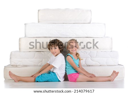 Young children sitting on lots of mattresses, isolated on white background - stock photo