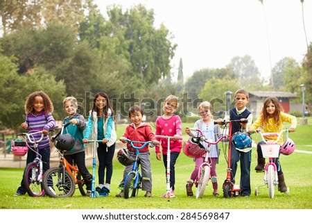 Young Children With Bikes And Scooters In Park - stock photo