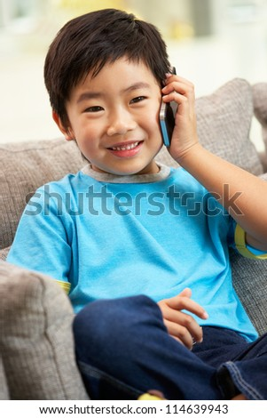 Young Chinese Boy Using Mobile Phone On Sofa At Home - stock photo