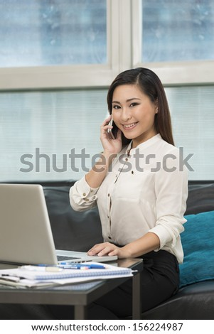 Young Chinese business woman working from home. Asian female using a laptop. - stock photo