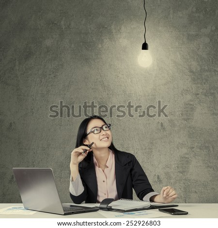 Young chinese businesswoman working at table while smiling happy and looking at lightbulb - stock photo