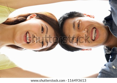 Young Chinese Couple Looking Down Into CameraTogether - stock photo