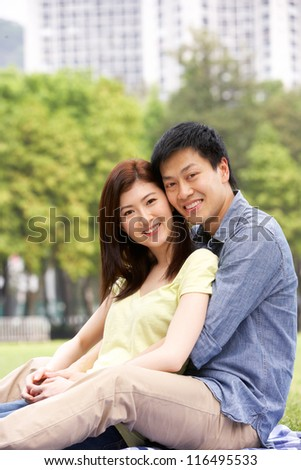 Young Chinese Couple Relaxing In Park Together - stock photo