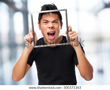 young chinese shouting through a frame - stock photo