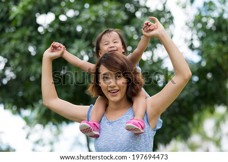 Young Chinese woman carrying her little daughter on shoulders - stock photo