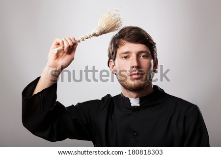 Young christian priest is holding a sprinkler - stock photo