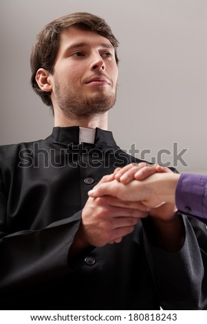 Young christian priest is holding believer hand - stock photo