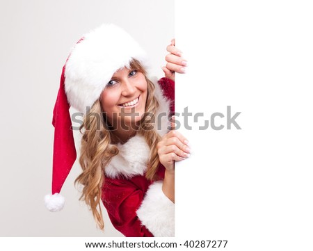 young christmas woman in red santa claus dress beside a copyspace label - stock photo
