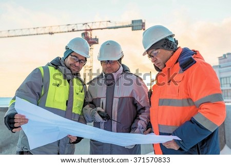 Young Civil Engineers and Senior Foreman at construction site are inspecting ongoing production according to design drawings. - stock photo