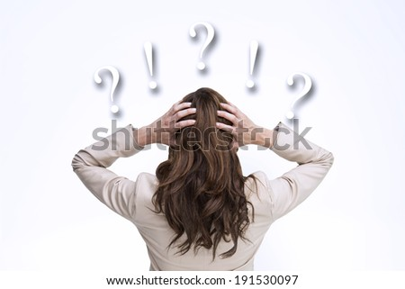 Young classy businesswoman with hands on head standing back to camera against question and exclamation marks - stock photo