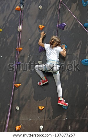 Young climber on an artificial wall, go to the top  - stock photo