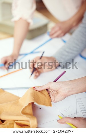 Young clothing designers draw on the sewing pattern - stock photo