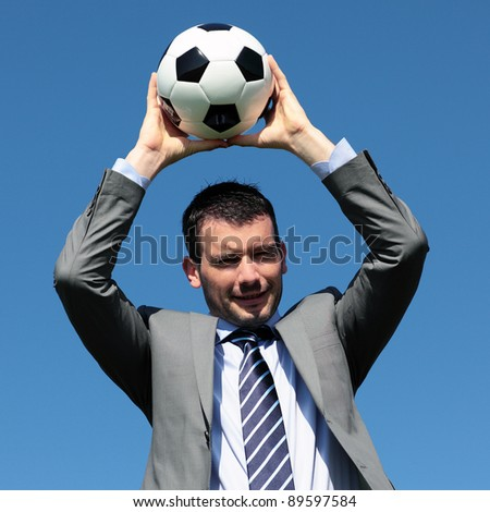 young coach with ball in blue sky - stock photo