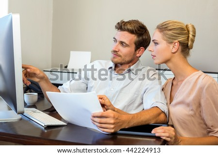 Young colleagues looking into computer while working in office - stock photo