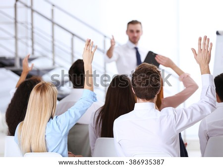 Young colleagues raising hands at the business meeting in office - stock photo