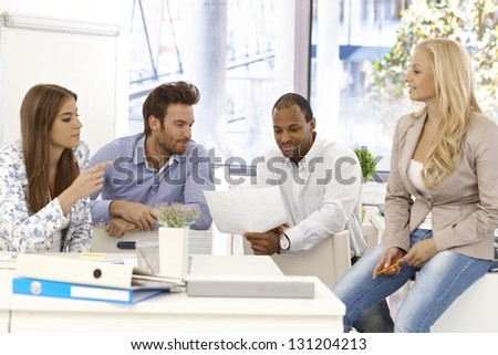 Young colleagues working together in bright office. - stock photo