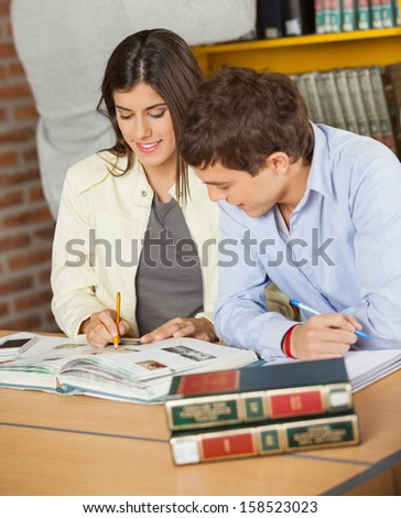 Young college friends studying together while student searching book in background at library - stock photo