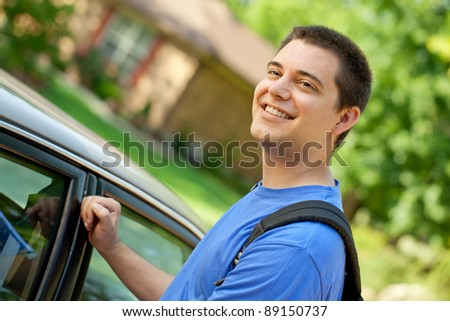 Young college man with backpack getting into his car - stock photo