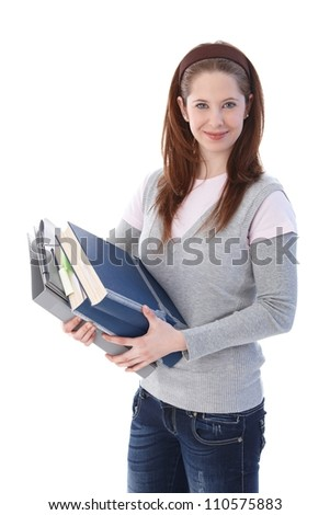 Young college student holding books in hands, smiling at camera. - stock photo