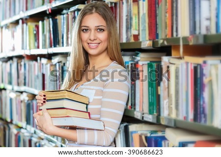 Young college woman in library holding books. - stock photo