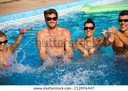 Young companionship splashing in outdoor swimming pool, having fun. - stock photo