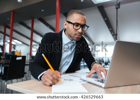 Young concentrated employee looking at computer monitor and noting during working day in office - stock photo