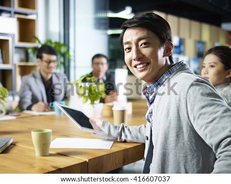 young confident asian businessman turning to look at camera during meeting in office. - stock photo