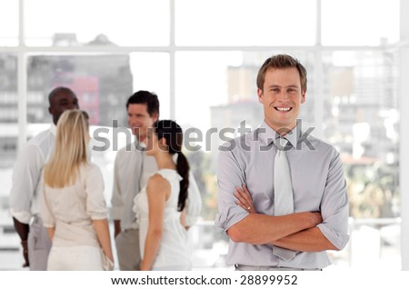 Young confident business man in front of a group of associates smiling - stock photo