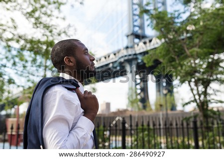 Young confident businessman portrait walking in Brooklyn Dumbo Park with Manhattan Bridge in the background. New York City. - stock photo