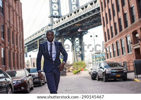Young confident businessman portrait with Manhattan Bridge in the background. Brooklyn, New York City. - stock photo