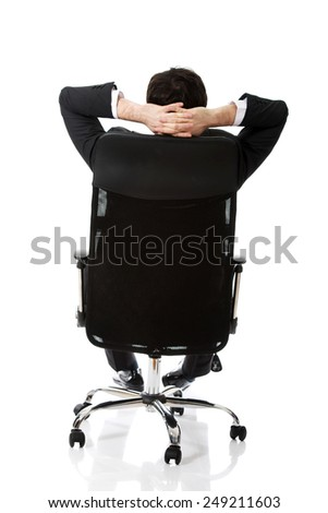 Young confident businessman resting on a chair. - stock photo