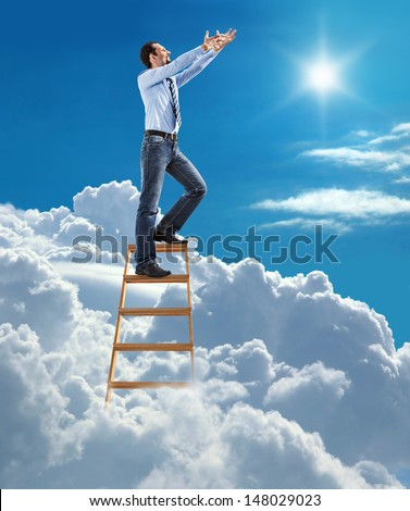 young confident businessman standing at the ladder high in the sky pulls hands to the sky / young man in shirt and tie pulls hands to the sky on top of the ladder on heaven  - stock photo