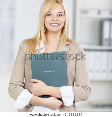 young confident candidate holding application folder in the office - stock photo