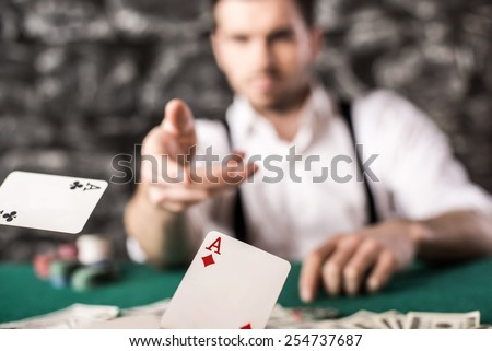 Young, confident, gangster man in shirt and suspenders, is throwing his cards on poker table, while he's playing poker game. - stock photo