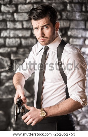 Young, confident, gangster pulls a revolver from the holster. - stock photo