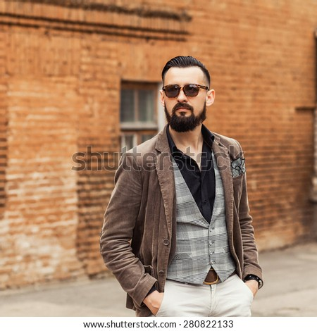 Young confident hipster man with beard in glasses posing on the street. Cute man wearing a vest, black shirt and light trousers. Man walks through the old town and looking forward - stock photo