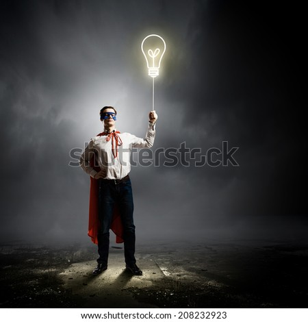 Young confident man in mask and cape - stock photo