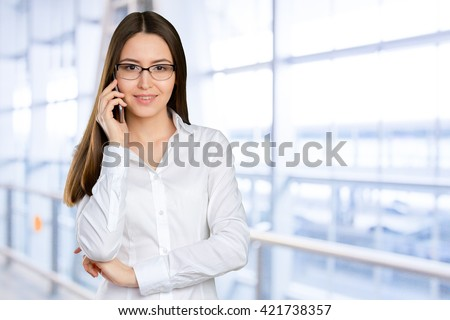 Young, confident, successful and beautiful business woman with the mobile phone isolated  - stock photo