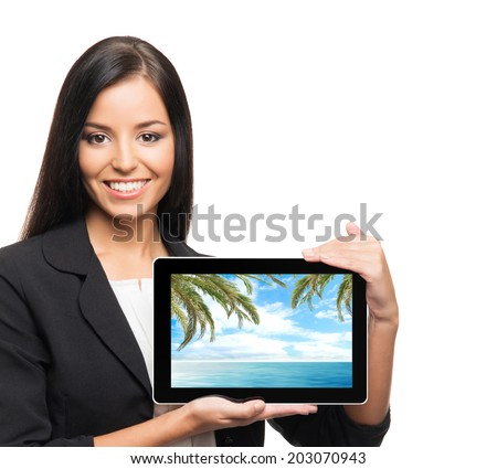 Young, confident, successful and beautiful business woman with the tablet computer showing the picture of summer resort - stock photo