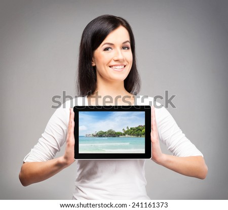 Young, confident, successful and beautiful girl with the tablet computer showing the picture of summer resort - stock photo