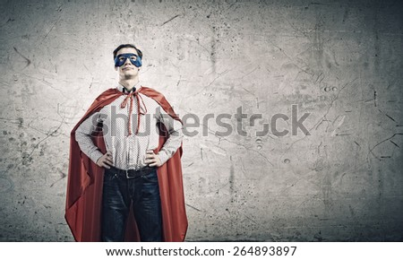 Young confident superman in mask and cape - stock photo
