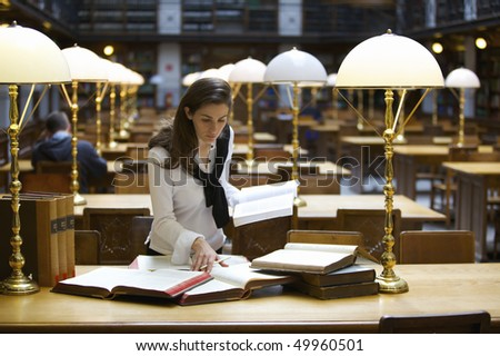 Young confident woman standing at desk in old university library studying books. - stock photo