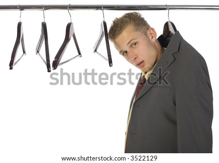 Young confused businessman hanging on hanger. Isolated on white in studio. Side view - stock photo