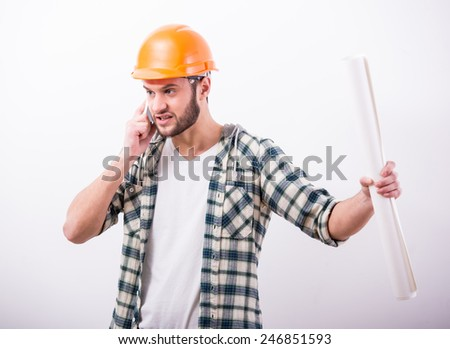Young construction man with a project on building is talking on phone. - stock photo
