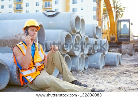 Young construction worker on cell phone at construction site - stock photo