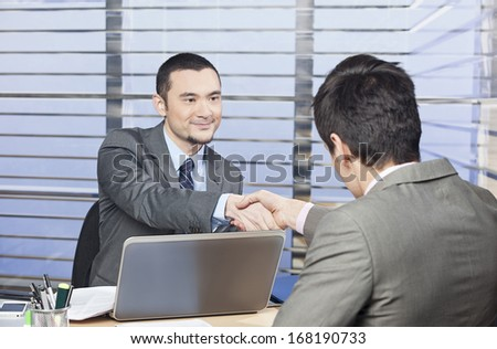 Young consultant shaking hands with his client - stock photo